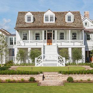 Diseño de fachada de casa blanca, costera, de tres plantas, con revestimiento de madera, tejado a cuatro aguas y tejado de teja de madera
