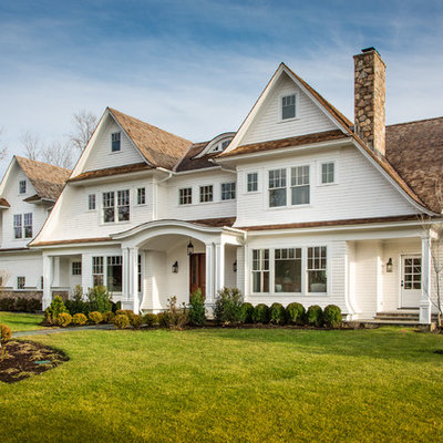 Inspiration for a large timeless white three-story wood exterior home remodel in New York with a shingle roof
