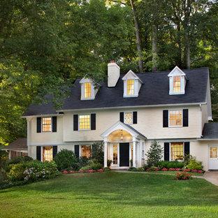 Diseño de fachada amarilla, clásica, de tres plantas, con revestimiento de madera