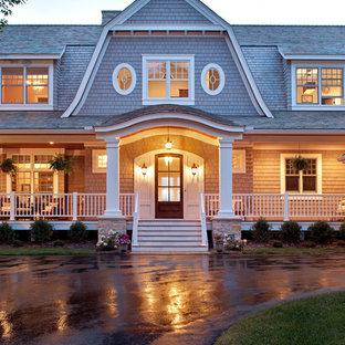 Ejemplo de fachada costera, de dos plantas, con revestimiento de madera y tejado a doble faldón