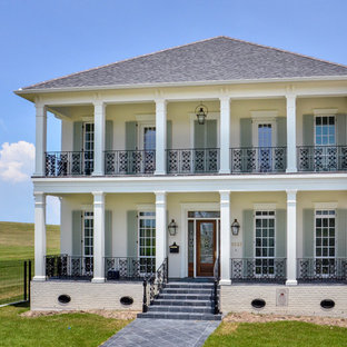 Large traditional white three-story brick exterior home idea in New Orleans