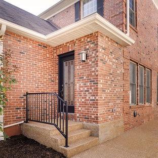 Ejemplo de fachada de casa marrón, actual, grande, de dos plantas, con revestimiento de ladrillo, tejado a doble faldón y tejado de teja de madera