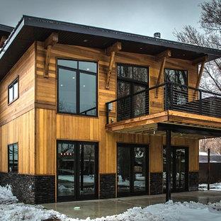 Ispirazione per la facciata di una casa unifamiliare marrone rustica a tre o più piani con rivestimenti misti, tetto a una falda e copertura in metallo o lamiera