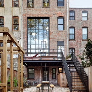 Inspiration for a large industrial brown three-story townhouse exterior remodel in New York