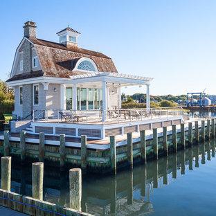 他の地域の小さいビーチスタイルのおしゃれな家の外観 (木材サイディング、グレーの外壁、混合材屋根) の写真