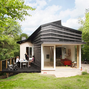 Photo of a mid-sized scandinavian two-storey black exterior in Copenhagen with wood siding and a flat roof.