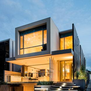 Imagen de fachada amarilla, contemporánea, pequeña, de tres plantas, con revestimiento de hormigón