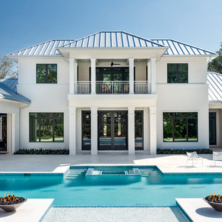 Example of a transitional white two-story house exterior design in Miami with a hip roof and a mixed material roof