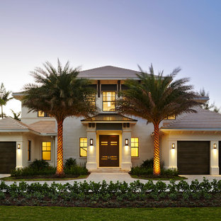 Large tropical white two-story stucco exterior home idea in Miami with a hip roof