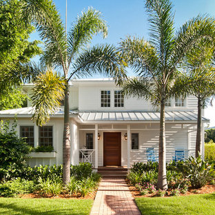 Example of an island style white two-story mixed siding exterior home design in Miami with a hip roof