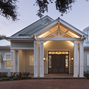 Large beach style white one-story vinyl house exterior idea in Orlando with a metal roof
