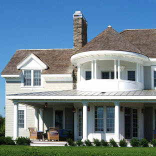 Example of an ornate wood exterior home design in Boston with a mixed material roof