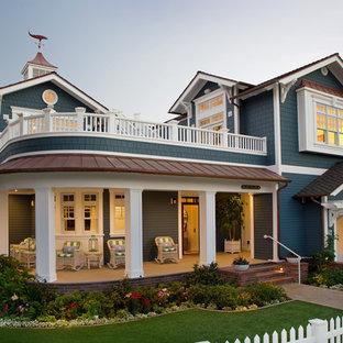 Imagen de fachada azul, costera, de dos plantas, con tejado a dos aguas y tejado de varios materiales
