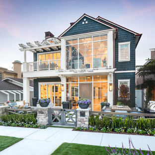 Example of a mid-sized coastal blue two-story wood exterior home design in Orange County with a shingle roof