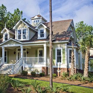 Diseño de fachada amarilla, tradicional, de dos plantas, con revestimiento de madera y tejado a dos aguas