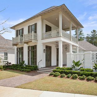 Inspiration for a mid-sized coastal beige two-story stucco exterior home remodel in New Orleans with a hip roof
