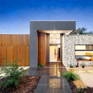 Foto della facciata di una casa ampia contemporanea a un piano con rivestimenti misti e tetto piano