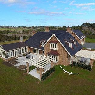 Ejemplo de fachada de casa naranja, rural, grande, de dos plantas, con revestimiento de ladrillo, tejado a cuatro aguas y tejado de teja de barro