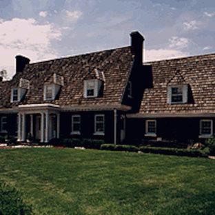 Modelo de fachada de casa negra, tradicional, grande, de dos plantas, con revestimiento de vinilo, tejado a doble faldón y tejado de teja de madera