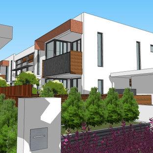 Свежая идея для дизайна: маленький, двухэтажный, белый дуплекс в современном стиле с облицовкой из крашеного кирпича, плоской крышей и металлической крышей - отличное фото интерьера