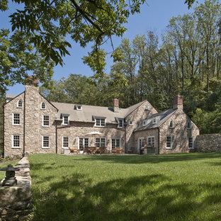 Foto della facciata di una casa unifamiliare grande marrone country a tre piani con rivestimento in pietra, tetto a capanna e copertura a scandole