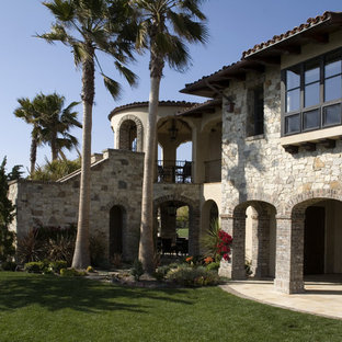 Inspiration for a mediterranean stone exterior home remodel in Orange County