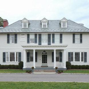 Esempio della villa bianca classica a due piani con tetto a padiglione e copertura a scandole