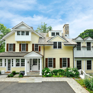 Example of a classic yellow three-story exterior home design in New York