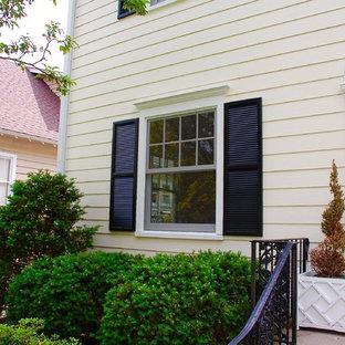 Esempio della facciata di una casa unifamiliare gialla classica a due piani di medie dimensioni con rivestimento con lastre in cemento, tetto a capanna e copertura a scandole