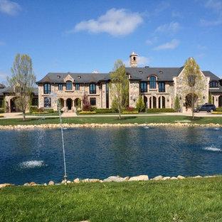 Foto de fachada de casa multicolor, de estilo americano, extra grande, de tres plantas, con revestimiento de piedra, tejado a doble faldón y tejado de teja de madera