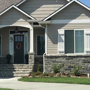 Example of a classic beige one-story mixed siding house exterior design in Other with a shingle roof