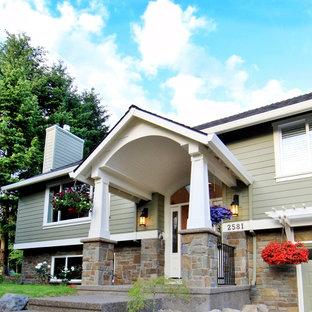На фото: большой, зеленый частный загородный дом в классическом стиле с разными уровнями, двускатной крышей, комбинированной облицовкой и крышей из гибкой черепицы