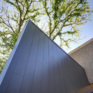 Пример оригинального дизайна: двухэтажный, черный многоквартирный дом среднего размера в стиле лофт с облицовкой из ЦСП, плоской крышей и черепичной крышей