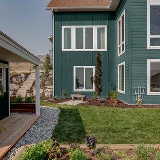Пример оригинального дизайна: большой, двухэтажный, зеленый частный загородный дом в стиле шебби-шик с комбинированной облицовкой, двускатной крышей и крышей из гибкой черепицы