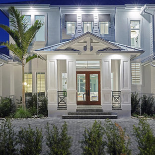 Large coastal white two-story concrete fiberboard house exterior photo in Miami with a hip roof and a metal roof