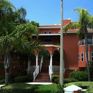 Example of a large tuscan red three-story stone exterior home design in Tampa with a hip roof