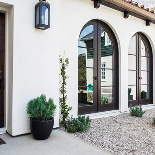 Example of a transitional white two-story adobe exterior home design in Los Angeles