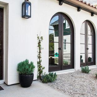 Inspiration pour une façade de maison blanche traditionnelle à un étage avec un revêtement en adobe.
