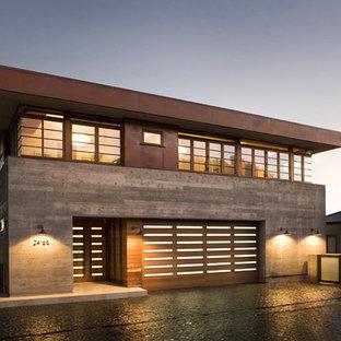 Imagen de fachada marrón, moderna, grande, de dos plantas, con revestimiento de hormigón y tejado plano