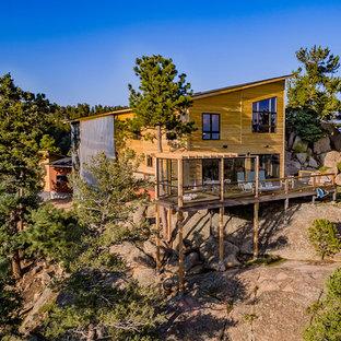 Imagen de fachada de casa amarilla, contemporánea, de tamaño medio, de dos plantas, con revestimiento de madera y tejado de un solo tendido