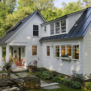 Inspiration for a small country two floor exterior in Burlington with wood cladding and a metal roof.