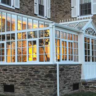 Modelo de fachada beige, clásica, grande, de dos plantas, con revestimiento de piedra y tejado a dos aguas