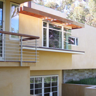 Example of a mid-sized trendy yellow split-level stucco flat roof design in San Luis Obispo