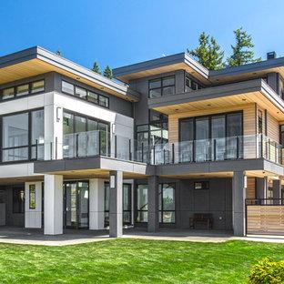 Bild på ett stort funkis flerfärgat hus, med blandad fasad, platt tak, två våningar och tak i metall