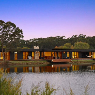 Inspiration for an expansive contemporary one-storey black house exterior in Sydney with wood siding and a flat roof.