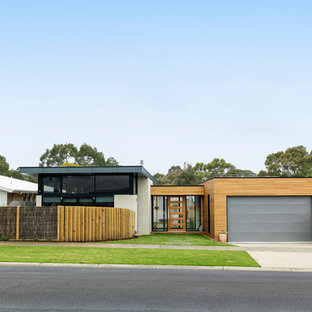 This is an example of a contemporary one-storey house exterior in Melbourne with mixed siding and a flat roof.