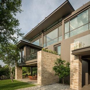 Esempio della facciata di una casa grigia contemporanea a due piani con rivestimenti misti e tetto piano