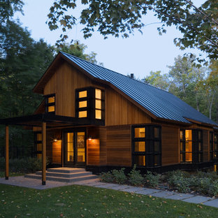 This is an example of a contemporary house exterior in Burlington with wood cladding and a pitched roof.