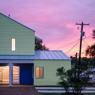 Exempel på ett modernt grönt hus, med två våningar och pulpettak