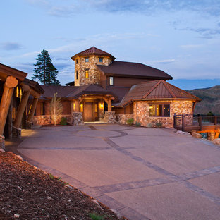 Photo of an expansive country split-level brown house exterior in Denver with stone veneer, a hip roof and a mixed roof.